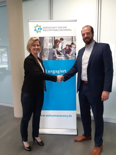 Andeas von Bismarck, chairman of the association Wirtschaft für ein weltoffenes Sachsen (right) welcomes Siltronic AG, represented by Ines Richter from the Freiberg plant's communication department, as a new member of the association.