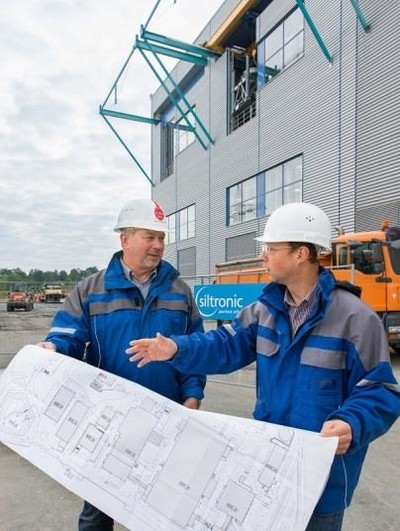 Siltronic project manager Johann Sperl (right) und Wacker Chemie project leader Gerhard Ofenmacher (left) in front of the new Siltronic pulling hall in Freiberg.